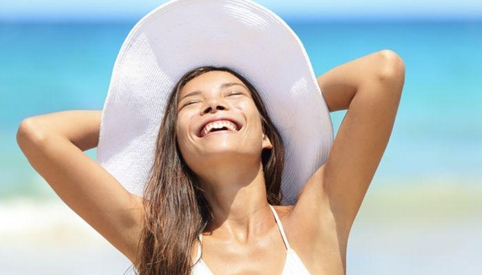 девушка счастливая веселая довольная в шляпе на пляже