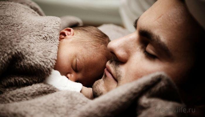 Отец спит с новорожденным ребенком